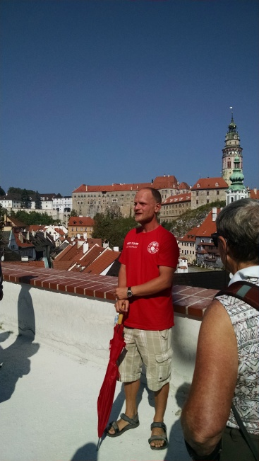 Walking tour guide with view of castle behind him.