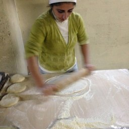 Woman #1 rolls out dough into long flat sections
