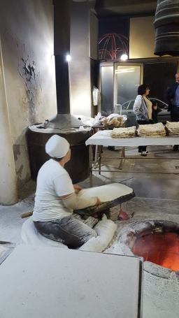 Woman #2 takes rolled dough and spreads it out on a large arm pad