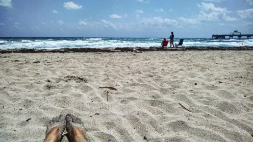 Laying on the beach, enjoying sunshine and warm water in Deerfield Beach, Florida.